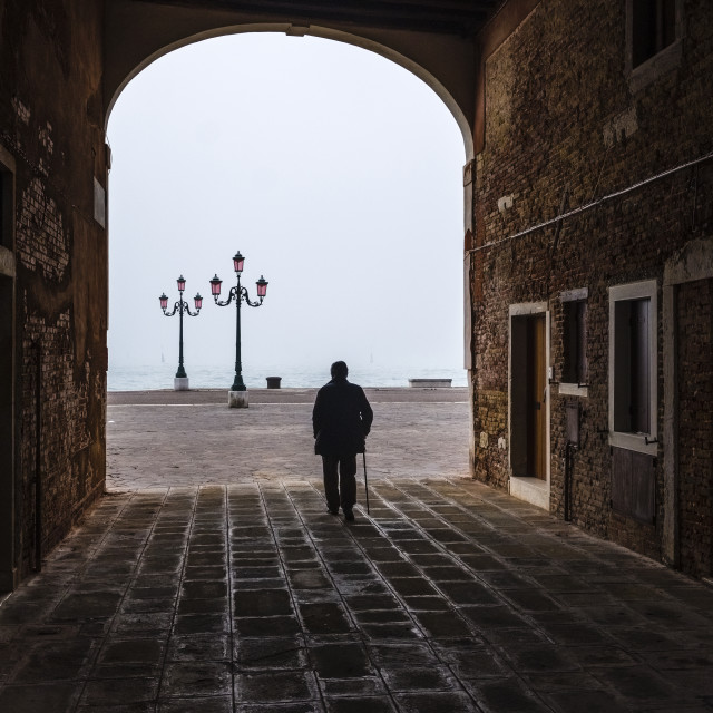 """""""Old man with a walking stick is walking through a gate between ailing brick houses of the so-called 'Floating city'"""" stock image"""