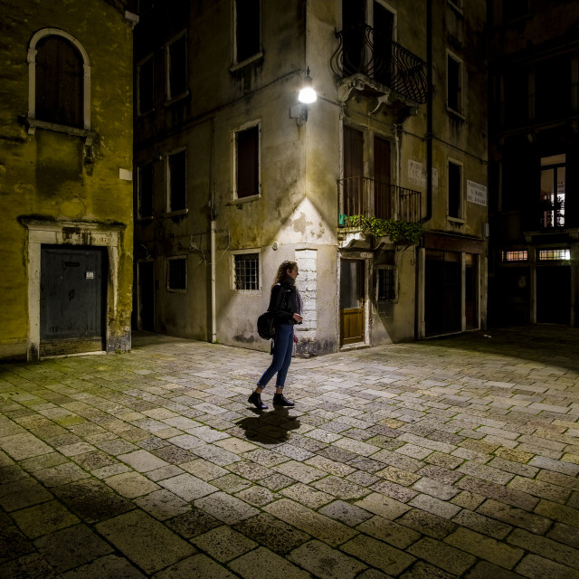 """""""A circle of light from a latern falling on a small square between the ailing brick houses of the so-called 'Floating city' at night, a women crossing"""" stock image"""