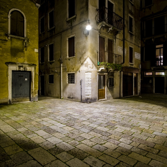 """""""A circle of light from a latern falling on a small square between the ailing brick houses of the so-called 'Floating city' at night"""" stock image"""