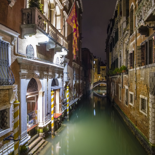 """""""Narrow water canals leading through the ailing brick houses of the so-called 'Floating city', illuminated at night"""" stock image"""