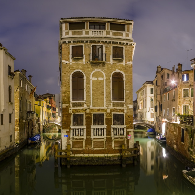 """""""Panoramic view on narrow water canals leading through the ailing brick houses of the so-called 'Floating city', illuminated at night"""" stock image"""