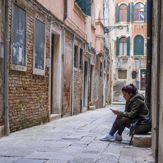 """""""Narrow streets leading through the ailing brick houses of the so-called 'Floating city', a woman is using her mobile phone"""" stock image"""