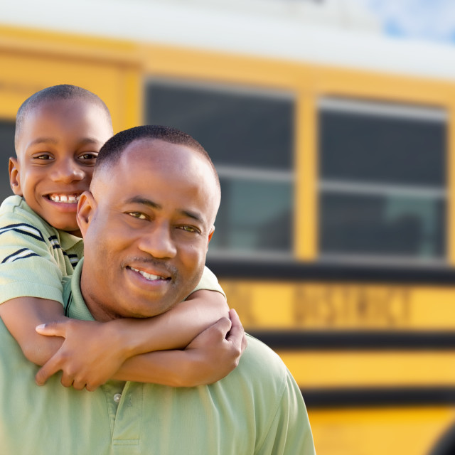 """African American Man and Child Piggyback Near School Bus"" stock image"