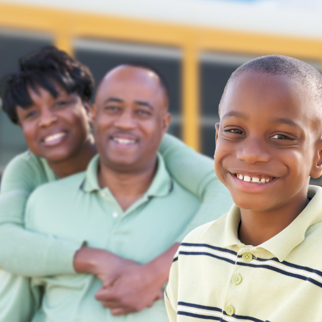 """Proud African American Parents and Young Boy Near School Bus"" stock image"
