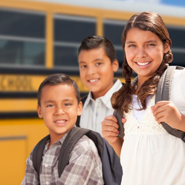 """Young Hispanic Girl and Boys Walking Near School Bus"" stock image"