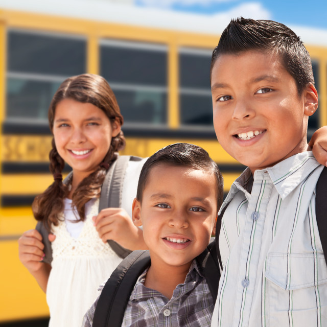 """Young Hispanic Boys and Girl Walking Near School Bus"" stock image"