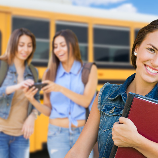"""Young Female Student with Books Near School Bus"" stock image"