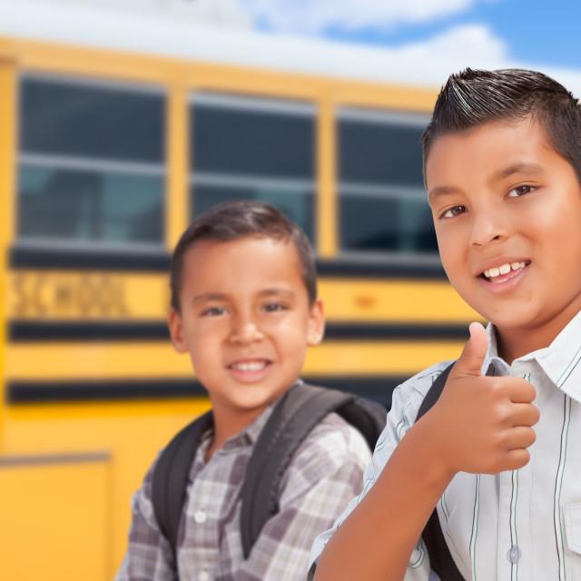 """Young Hispanic Boys Walking Near School Bus"" stock image"