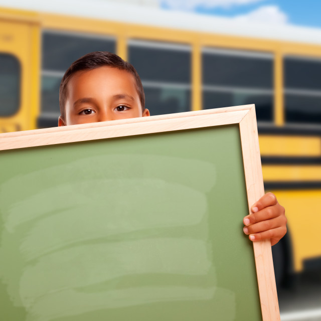 """Young Hispanic Boy with Blank Chalkboard Near School Bus"" stock image"