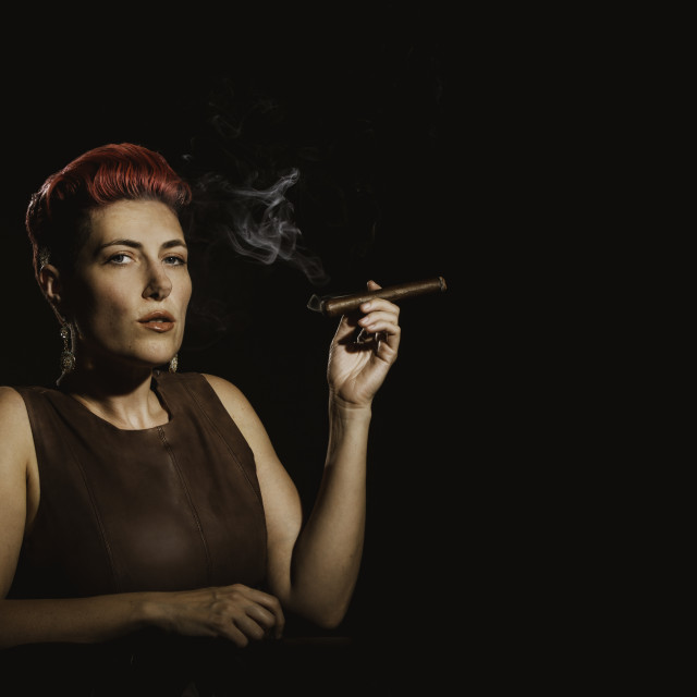 """Modern Woman Smoking a Lit Cigar"" stock image"