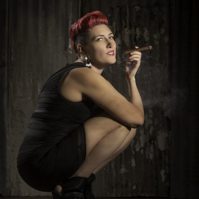 """Modern Woman Blowing Smoke from a Cigar"" stock image"