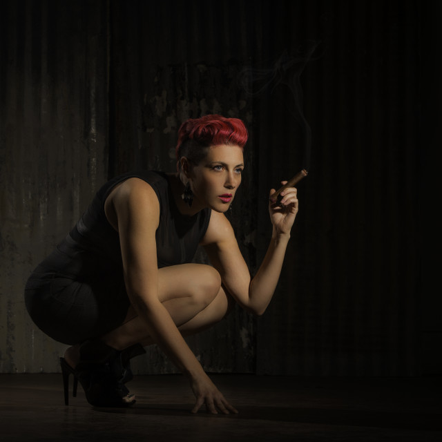 """Modern Woman Crouching with a Cigar"" stock image"