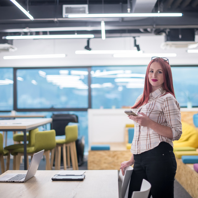 """""""redhead businesswoman using mobile phone at office"""" stock image"""