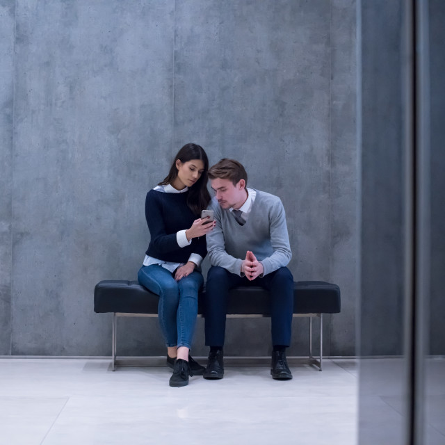"""""""business couple using mobile phone while sitting on the bench"""" stock image"""