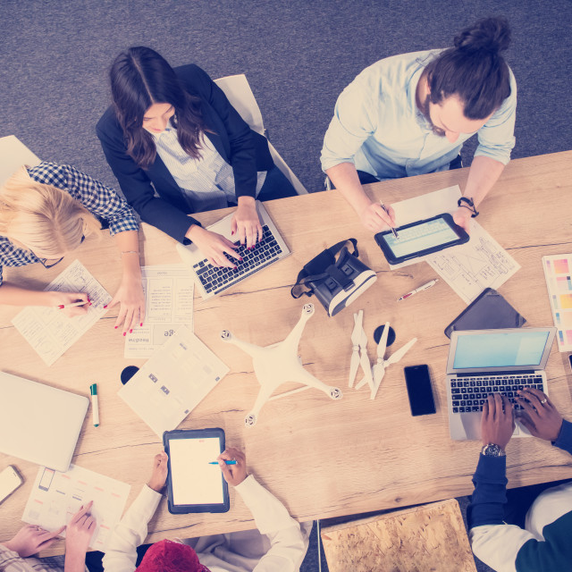"""""""top view of multiethnic business team learning about drone technology"""" stock image"""