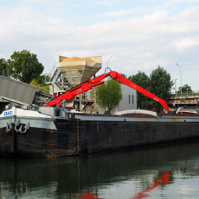 """A barge is moored close to a crane"" stock image"