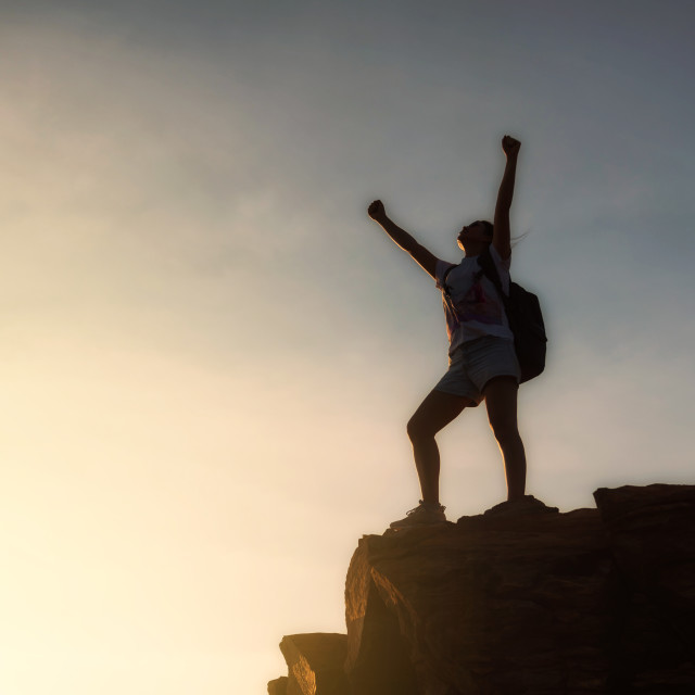 """woman backpacker victory pose at mountain summit"" stock image"
