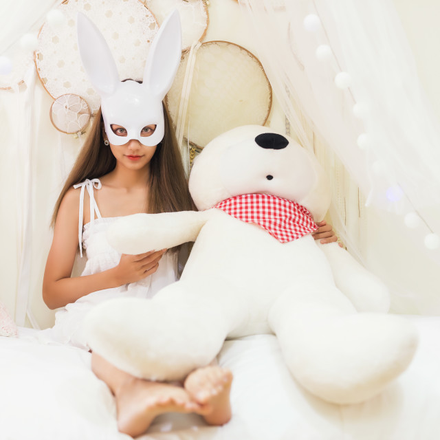 """brunette woman with rabbit mask hold big bear"" stock image"