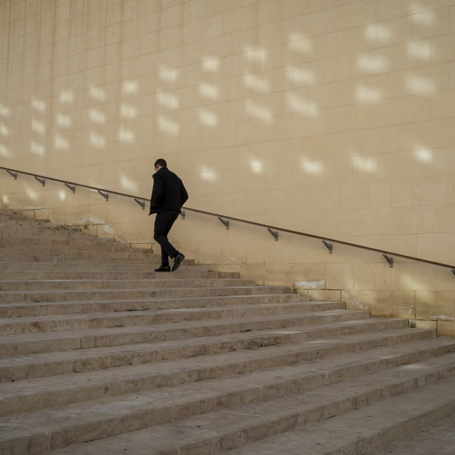 """man walking up stone steps, Valletta, Malta."" stock image"