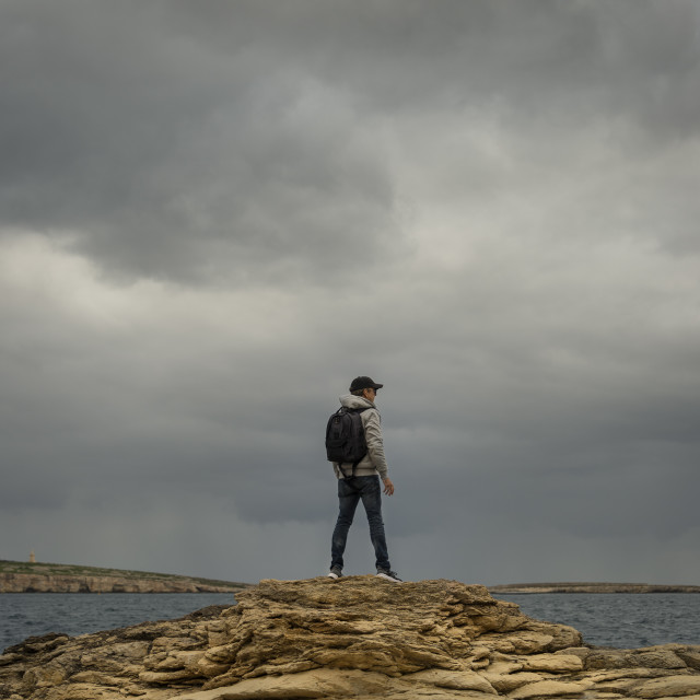 """""""man with backpack standing on top of rocks looking out to sea, moody sky."""" stock image"""