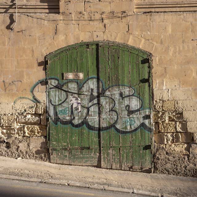 """old weathered green garage door in a street in Silema, Malta."" stock image"