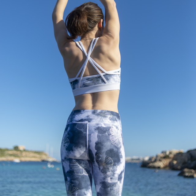 """""""woman doing stretching execises by the sea, back view"""" stock image"""