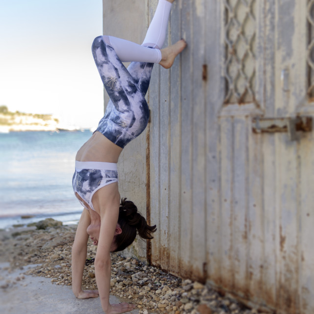 """""""Woman practicing yoga, doing a handstand against a wall outside"""" stock image"""
