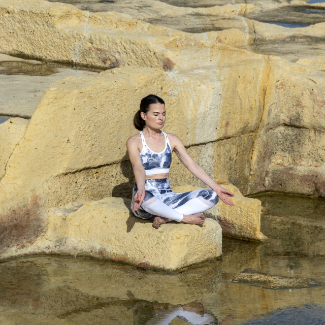 """""""woman meditating, practicing the 'easy pose' amongst the limestone salt pans in Malta"""" stock image"""