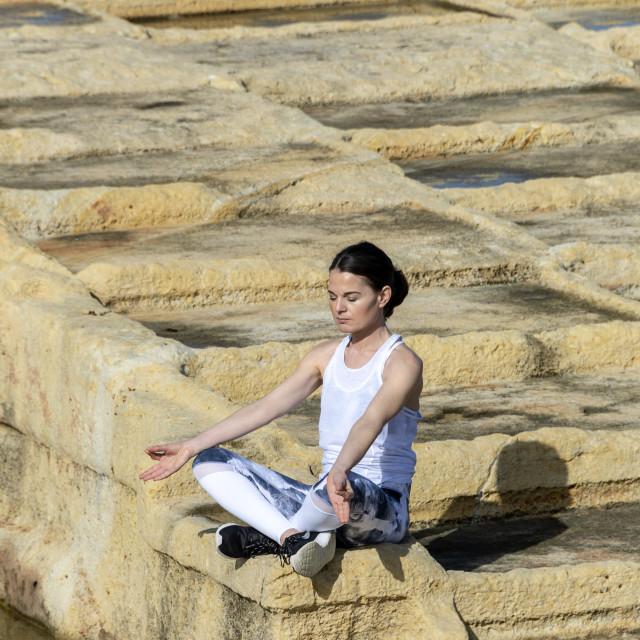 """woman meditating, sitting amongst the limestone salt pans in Malta"" stock image"