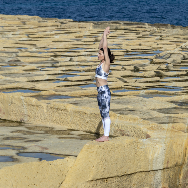 """""""woman meditating, practicing the 'mountain pose' amongst the limestone salt pans in Malta"""" stock image"""