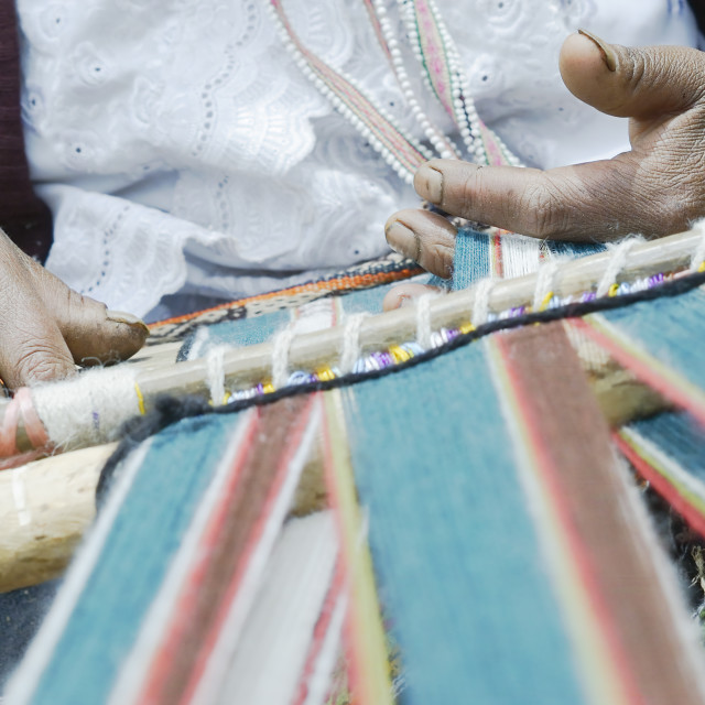 """Peruvian woman weaving cloth on a hand loom"" stock image"