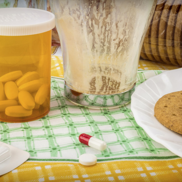 """""""Medication during breakfast, capsules next to a glass of water, conceptual..."""" stock image"""