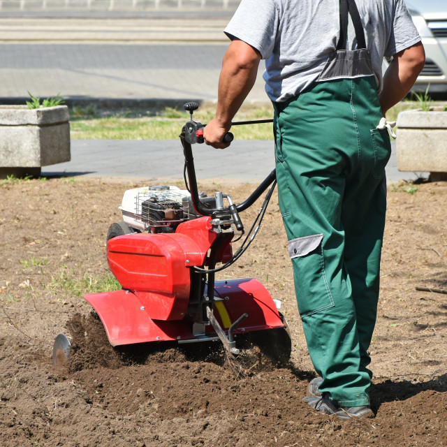"""Gardener works with a tiller machinery"" stock image"