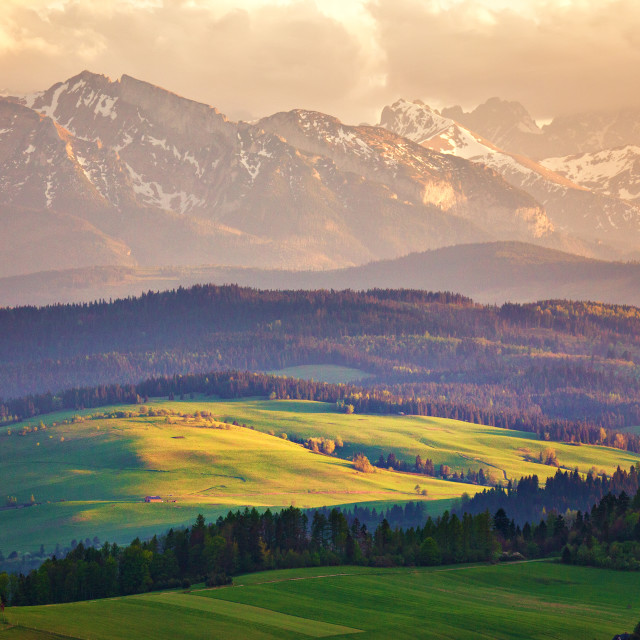 """""""Snow caped mountains and green fields and meadows"""" stock image"""