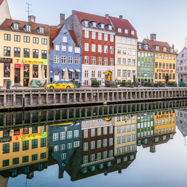 """Reataurants on the quay of Nyhavn Canal reflecting in the calm w"" stock image"