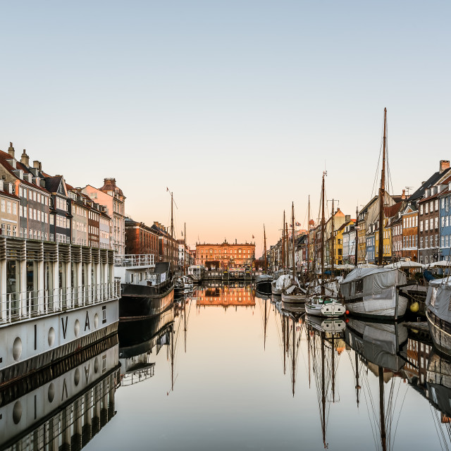 """Sunrise over the calm water at Nyhavn harbor in Copenhagen, Feb"" stock image"
