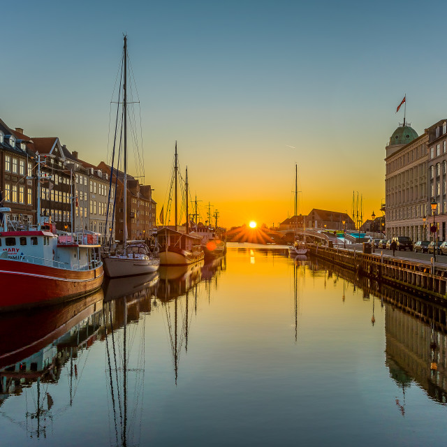 """The Copenhagen Nyhavn Canal and the sunrise over the calm water"" stock image"