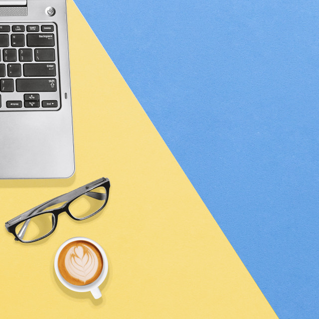 """Modern desk office with laptop, notebook, eyeglasses and hot coffee with copy space"" stock image"