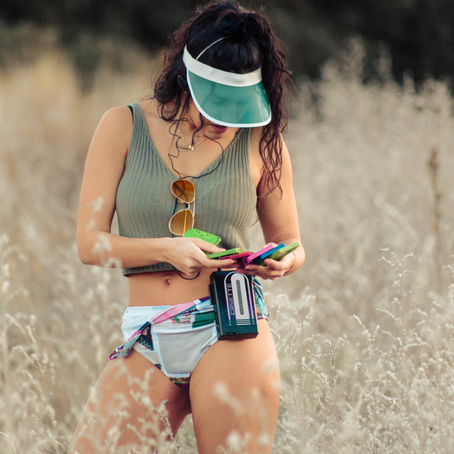 """""""Young brunette woman selecting old cassettes in the field"""" stock image"""