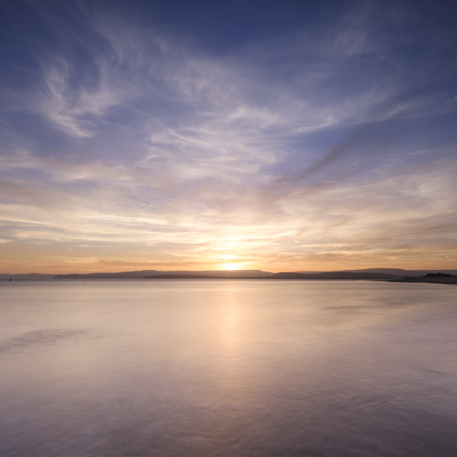 """""""With interesting wispy clouds, the sun sets across the water from Exmouth,..."""" stock image"""