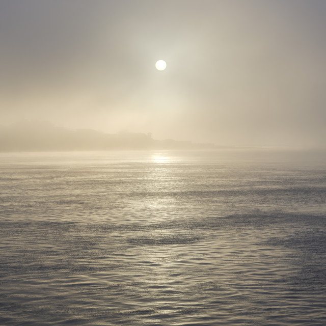 """""""The sun shines through heavy fog on the sea front at Exmouth, Devon, UK"""" stock image"""