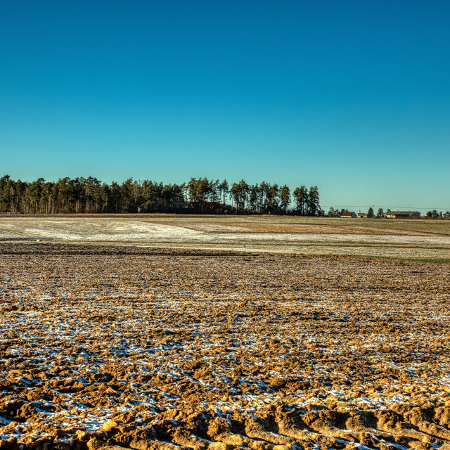 """Plowed fields sprinkled with snow"" stock image"
