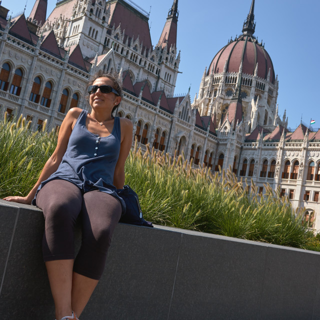 """Beautiful young Spanish woman sitting in front of the Parliament of Hungary"" stock image"