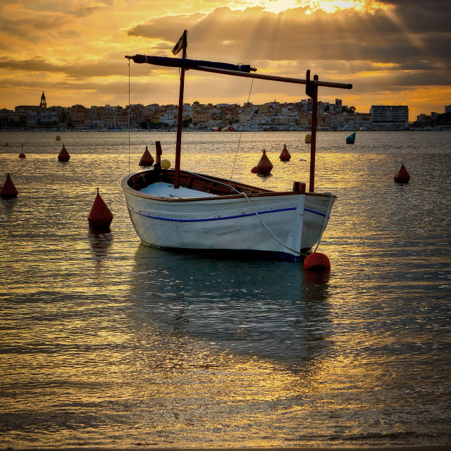 """Beautiful orange colors early in the morning in Spain with a traditional Spanish boat"" stock image"