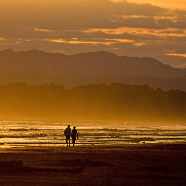 """Couple on the beach at dawn"" stock image"