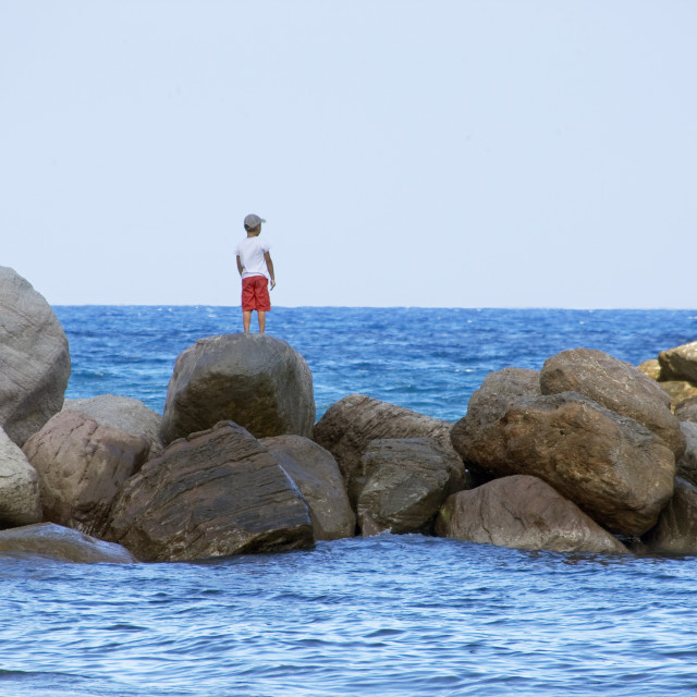 """Boy staring out to sea."" stock image"