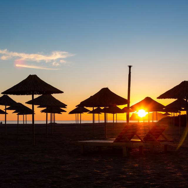 """""""Sunset in holiday resort with umbrellas on beach"""" stock image"""