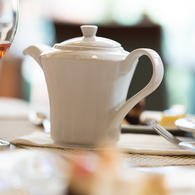 """""""Teapot on table in luxury restaurant next to glass with rose win"""" stock image"""