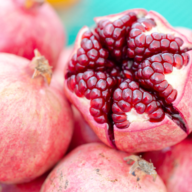 """""""Cut in half, peeled pomegranate with bold seeds on market stall"""" stock image"""