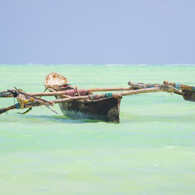 """Dhow wooden boat in a tropical clear blue sea at the Indian Ocean"" stock image"